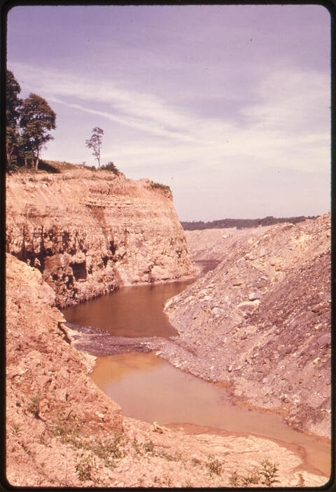 Erik Calonius - Buttes, Mesas and Canyons Are Created after Coal Companies Strip Mine Land in Southeastern Ohio. Trapped Water Has Been Discolored by Acidity Off Route #800 1974