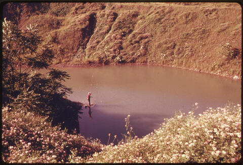 Erik Calonius - Fisherman Makes A Catch in A Body of Water Left in A 20-Year-Old Strip Mining Pit Off Route #519 1974