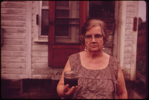 Erik Calonius - Mary Workman Holds A Jar of Undrinkable Water That Comes from Her Well, and Has Filed A Damage Suit Against the Hanna Coal Company, 1973
