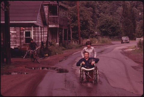 Jack Corn - Jack Smith, 42, a Disabled Miner in Rhodell, West Virginia, Is Wheeled Down the Street by His Daughter, Donna, 16, to the Beer Joint He Operates, 1974