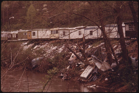 Jack Corn - Row of Mobile Homes near Madison, West Virginia, with Trash Thrown Along the Edge of the Creek 1974